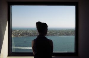 Woman looking out of aluminium window at sea